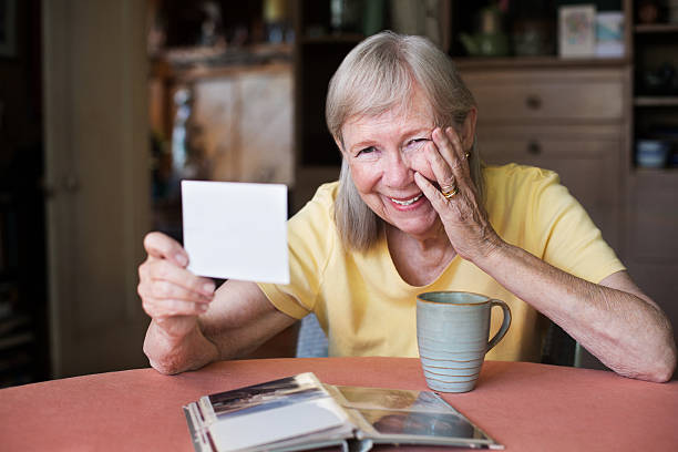 Laughing woman looking at photo - foto stock