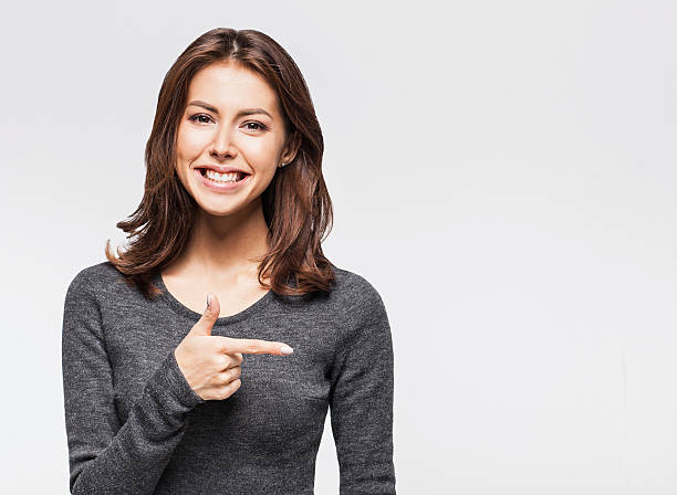 laughing woman pointing at copy space - finger point stock photos and pictures