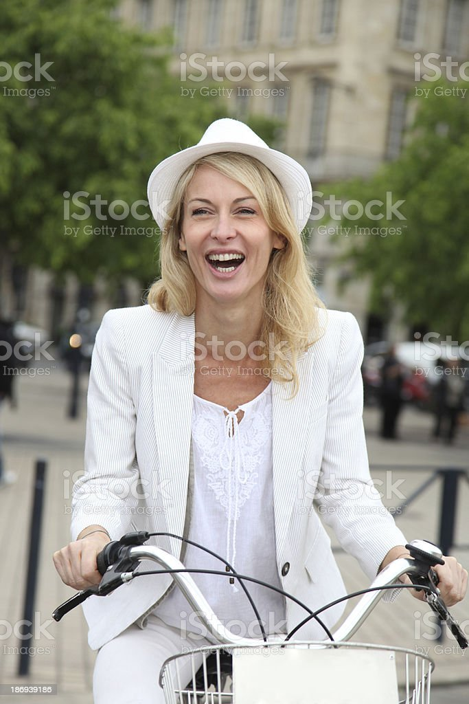 Laughing woman riding bicycle in city royalty-free stock photo