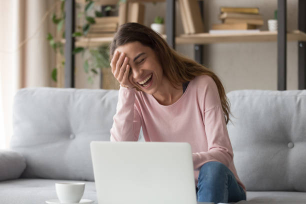 Laughing woman sitting on couch watching comedy movie on laptop Laughing woman sitting on sofa watch comedy movie on pc enjoy funny videos stand up show online program listens comic feels overjoyed, weekend activities at home, wireless tech internet usage concept laughing stock pictures, royalty-free photos & images