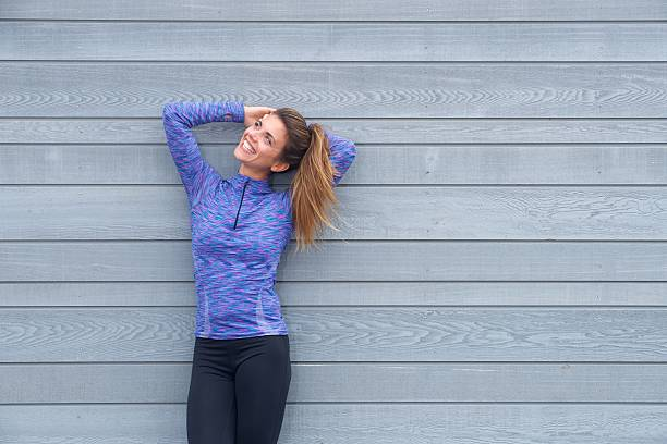 Laughing woman standing with hands behind head - foto de stock