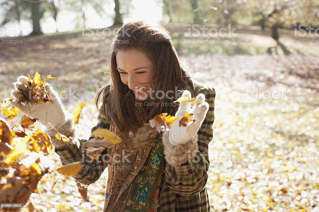 Laughing woman throwing autumn leaves royalty free stockfoto
