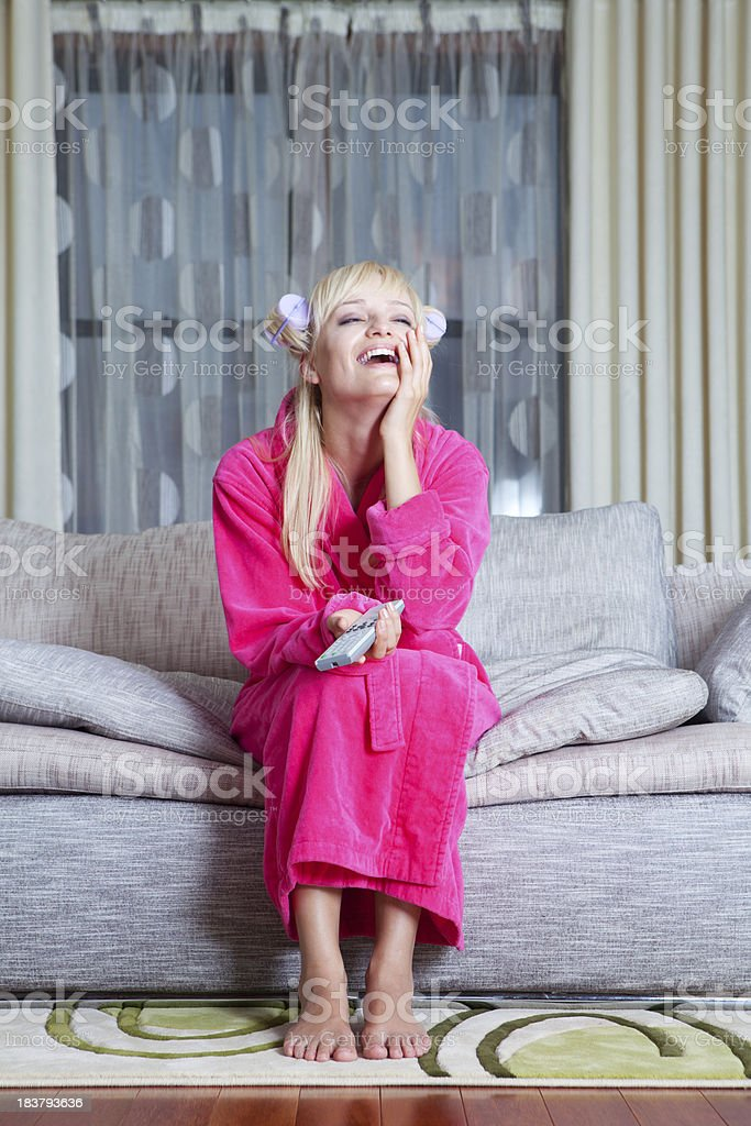 Laughing woman watching TV at home royalty-free stock photo