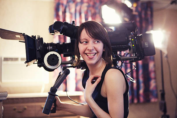 laughing woman with camera - film director stock pictures, royalty-free photos & images