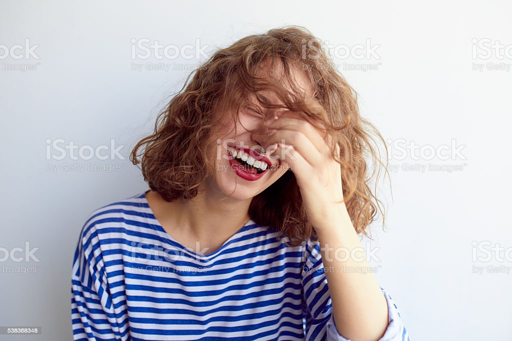 Laughing woman with curly hair on white wall stock photo