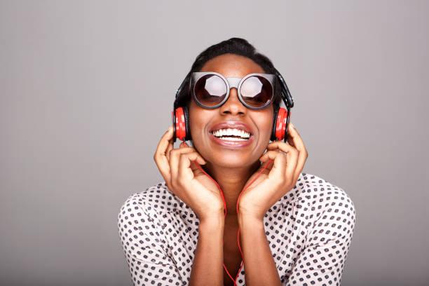 Lachende Frau mit Sonnenbrille Musik über Kopfhörer hören – Foto