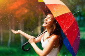 istock Laughing woman with umbrella checking for rain 178999468