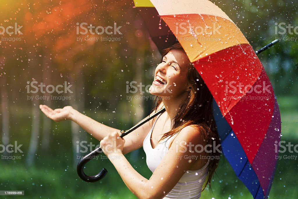 Laughing woman with umbrella checking for rain stock photo