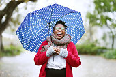 Shot of a cheerful young woman under an umbrella outdoors in rain