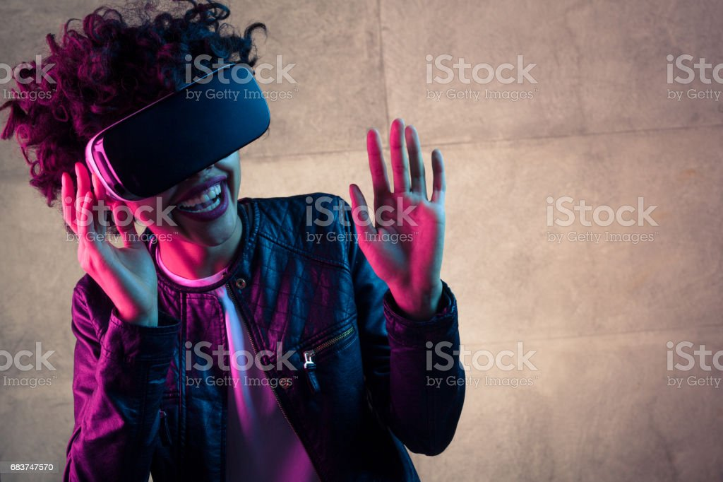 Laughing woman with VR goggles stock photo