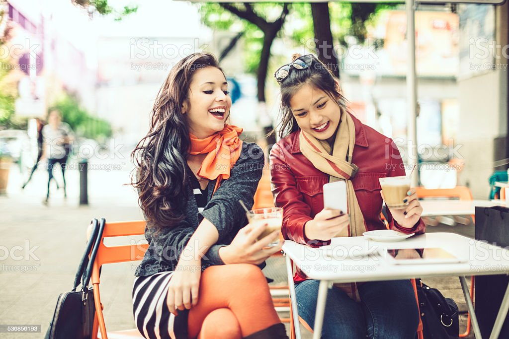 Laughing women are texting in a cafe stock photo