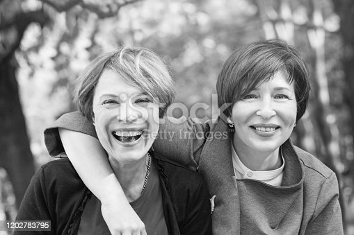 Laughing women hugging and having fun in park, tonned black and white retro portrait