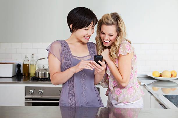 笑う女性の携帯電話を使用して - イギリス ストックフォトと画像