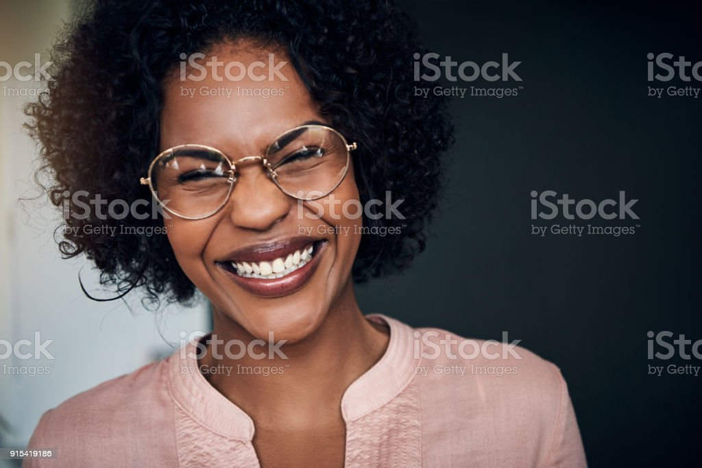 Laughing young African businesswoman standing alone in a modern office Young African businesswoman wearing glasses and lauging while standing alone in a modern office Adult Stock Photo