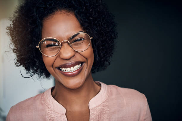 Laughing young African businesswoman standing alone in a modern office stock photo