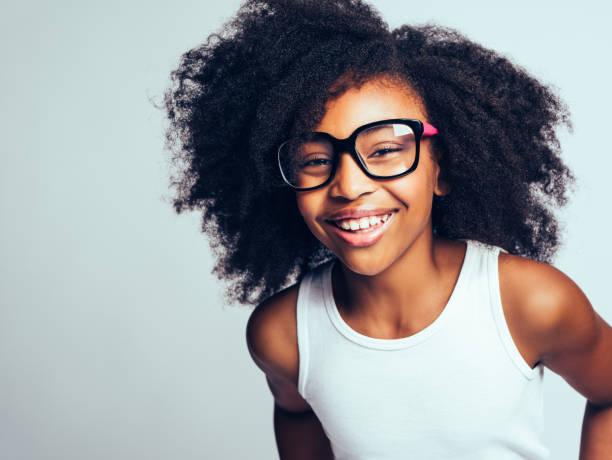 junge afrikanische mädchen mit brille vor einem grauen hintergrund lachen - kind vor der pubertät stock-fotos und bilder