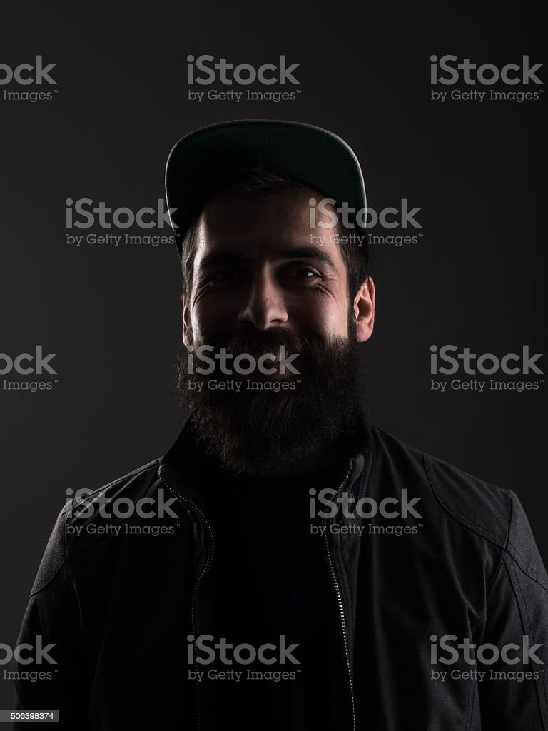 Laughing young bearded man with baseball cap looking at camera stock photo
