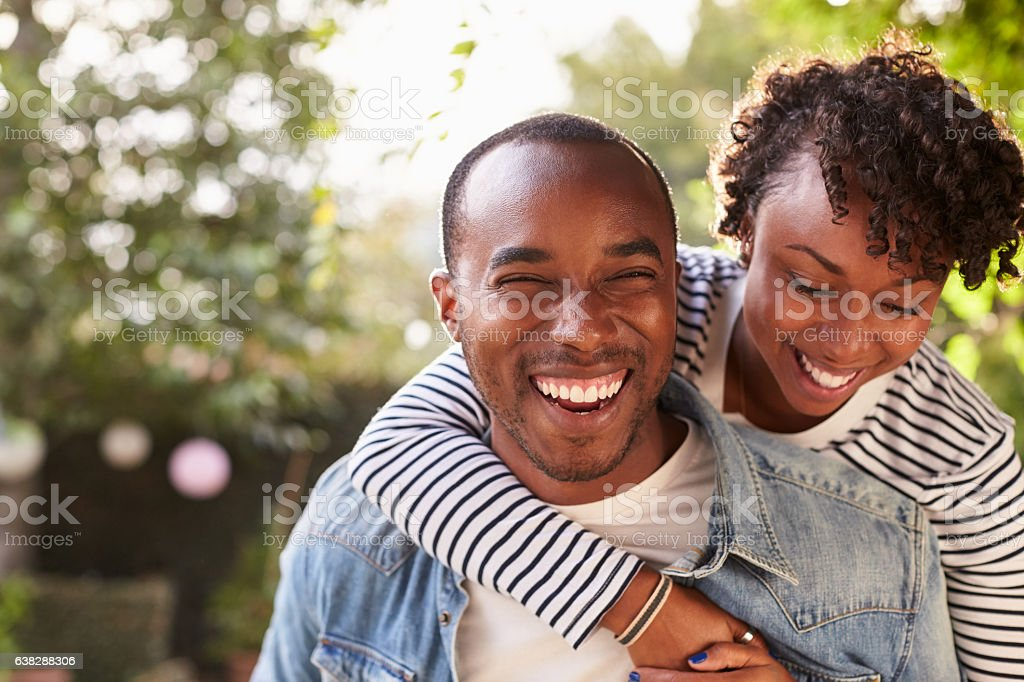 Laughing young black couple piggyback in garden, to camera stock photo