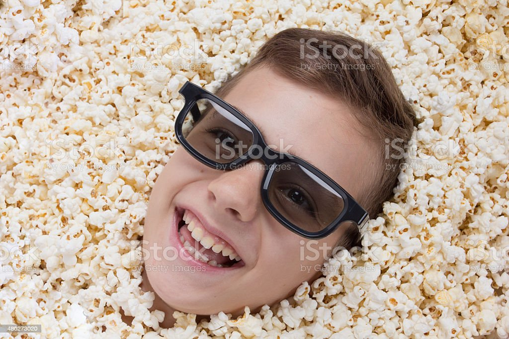 Laughing young boy in stereo glasses looking out of popcorn stock photo