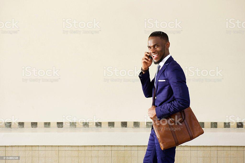 Rindo jovem homem de negócios, andando e falando no telefone celular - foto de acervo