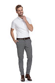 istock laughing young casual man adjusting collar and looking away 1131989508