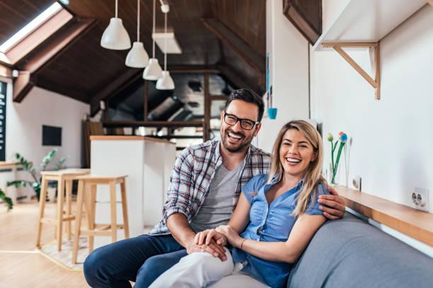 skrattar unga paret sitter i soffan på sin nya moderna lägenhet. - nygift bildbanksfoton och bilder
