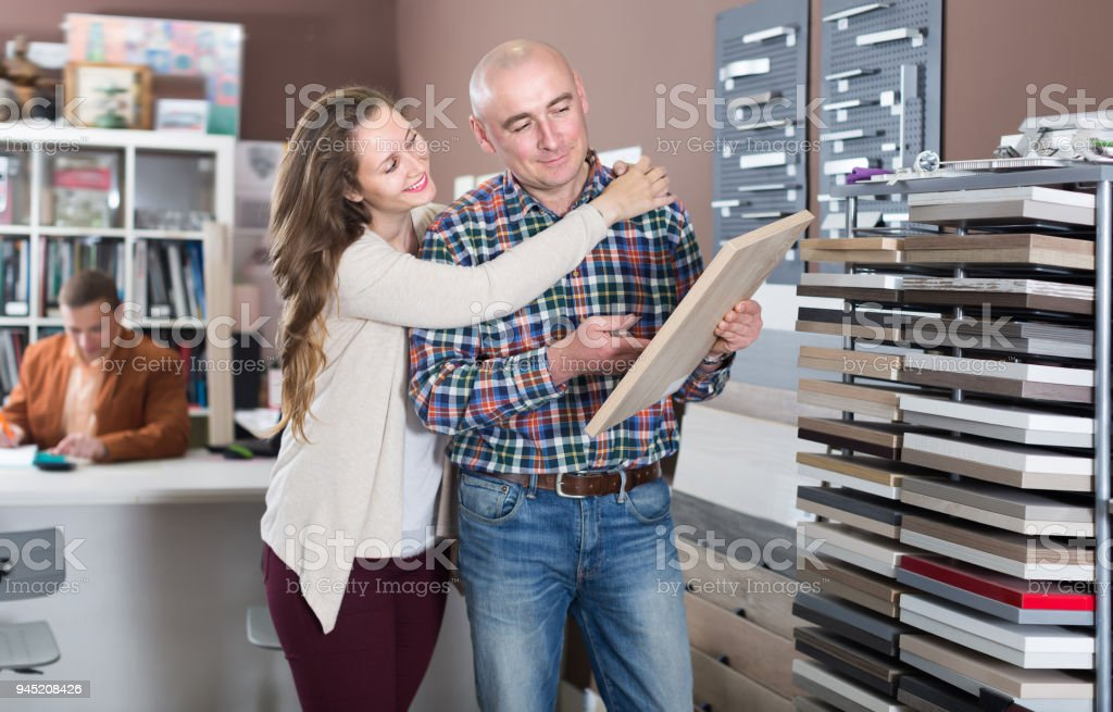 Laughing young customers choosing kitchen facade stock photo