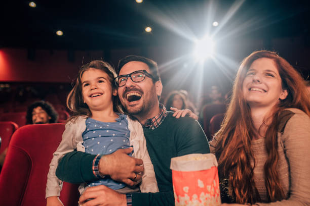 Laughing young family at cinema stock photo