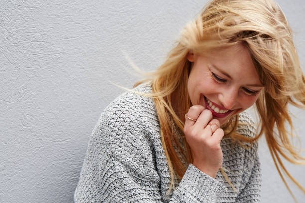 Laughing young lady Laughing young blond lady in grey one young woman only stock pictures, royalty-free photos & images