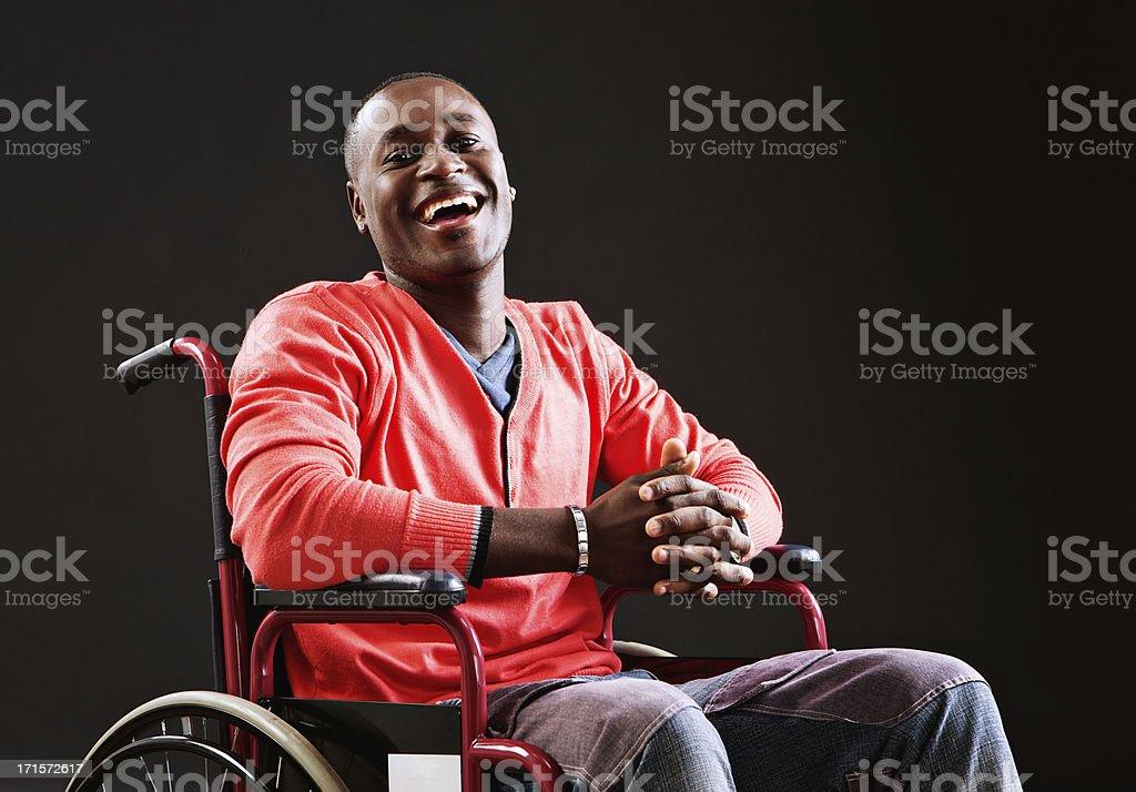 Sonriente joven hombre en silla de ruedas, acepta su situación - foto de stock
