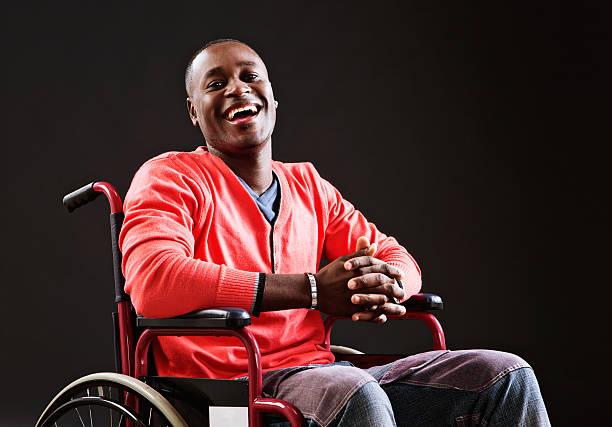 Rire jeune homme en fauteuil roulant accepte sa situation - Photo