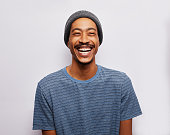 Studio portrait of a young man wearing a t-shirt and hat laughing against a gray background