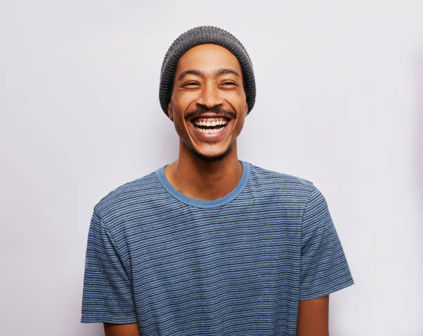 Laughing young man standing against a gray background Studio portrait of a young man wearing a t-shirt and hat laughing against a gray background excited stock pictures, royalty-free photos & images