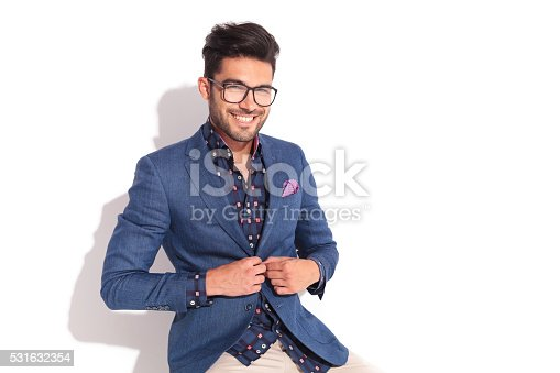 istock laughing young man unbuttoning his coat 531632354