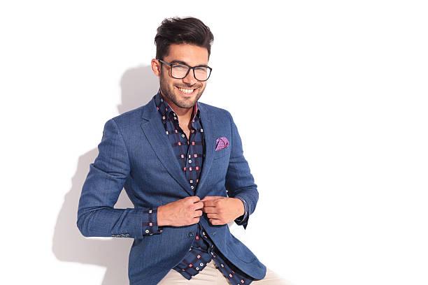笑う若い男性 unbuttoning 彼のコート - 男性のファッション ストックフォトと画像