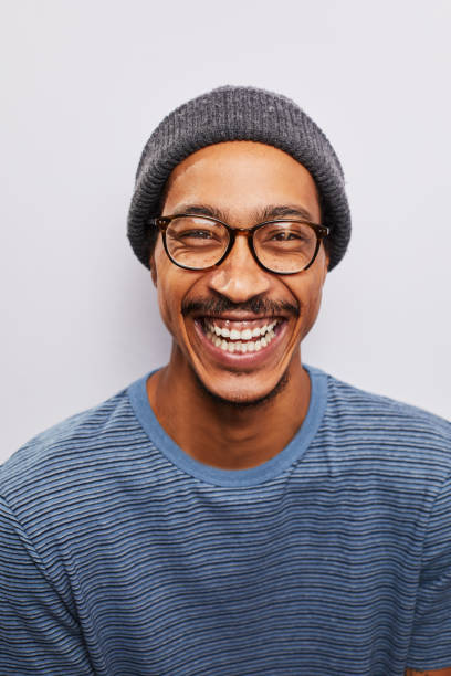 Laughing young man wearing glasses standing against a gray background stock photo