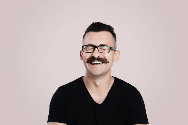 Laughing young man with mustache Young male with glasses and mustache, grey background, studio shot, laughing making a face stock pictures, royalty-free photos & images
