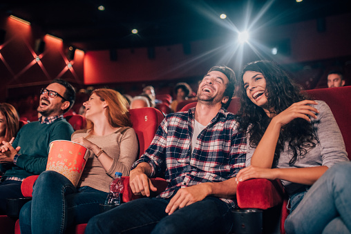 Happy four friends at cinema together