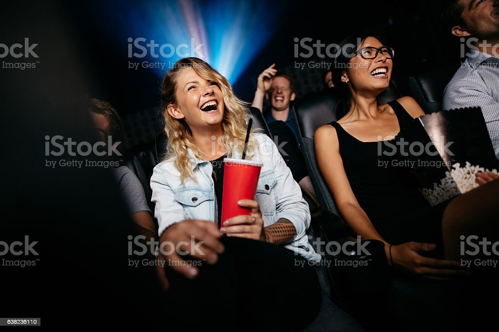 Laughing young people watching film in theater stock photo