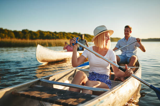 Laughing young woman canoeing on a lake with friends Young woman laughing while paddling a canoe on a lake with her boyfriend and another couple on a sunny summer afternoon canoeing stock pictures, royalty-free photos & images
