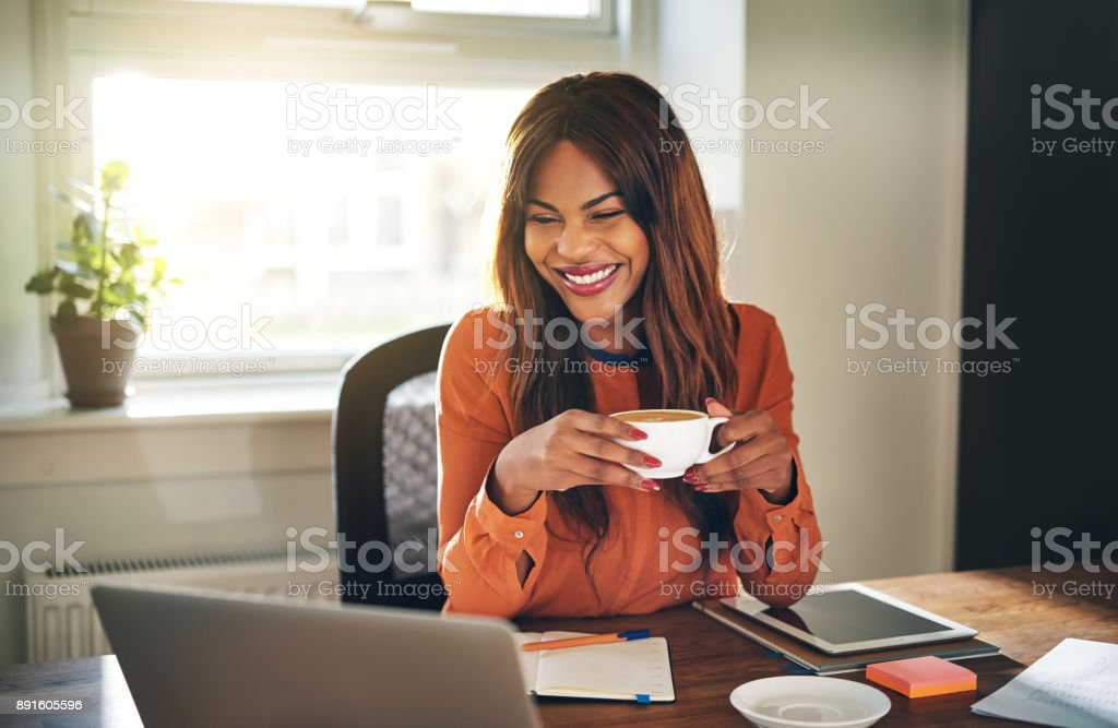Laughing young woman drinking coffee while working from home stock photo