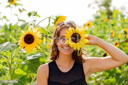 Laughing young woman holds a sunflower in front of her eyes.