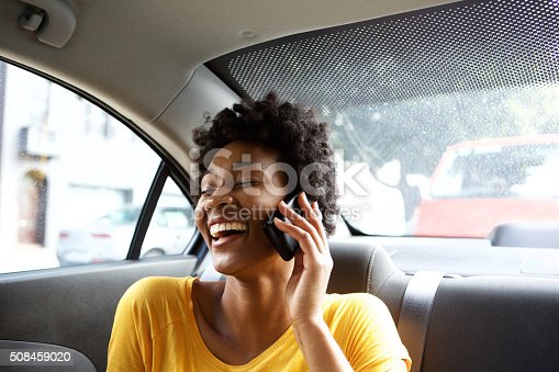 istock Laughing young woman in a car talking on mobile phone 508459020