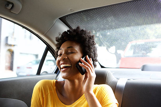 Laughing young woman in a car talking on mobile phone Closeup portrait of laughing young african woman sitting on a back seat of a car and talking on mobile phone passenger stock pictures, royalty-free photos & images