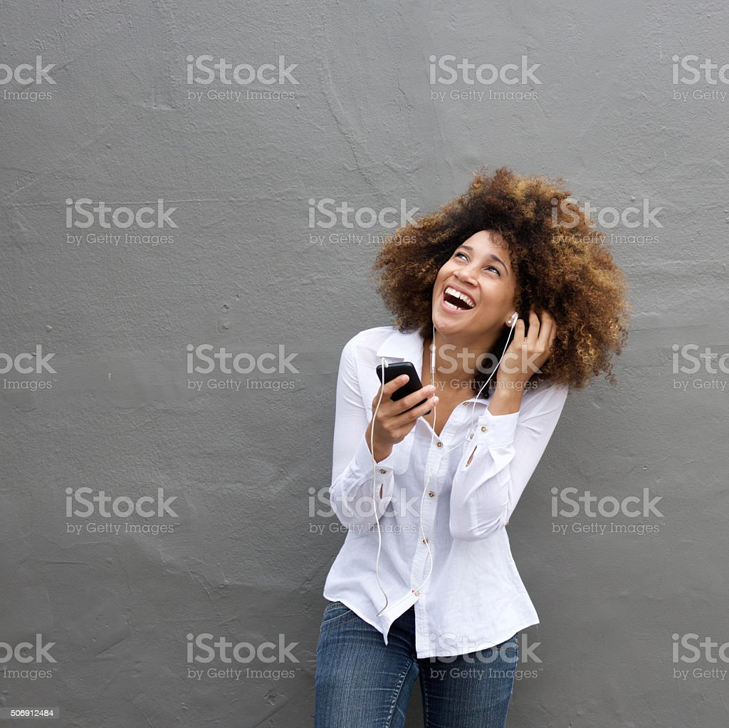 Portrait of young african female laughing with earphones and cell...