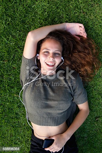 Portrait from above laughing young woman lying on grass listening to music