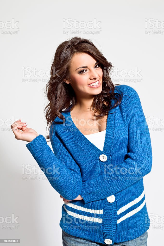 Laughing young woman Portrait of pretty young woman wearing blue cardigan, laughing at camera. Studio shot. 20-24 Years Stock Photo