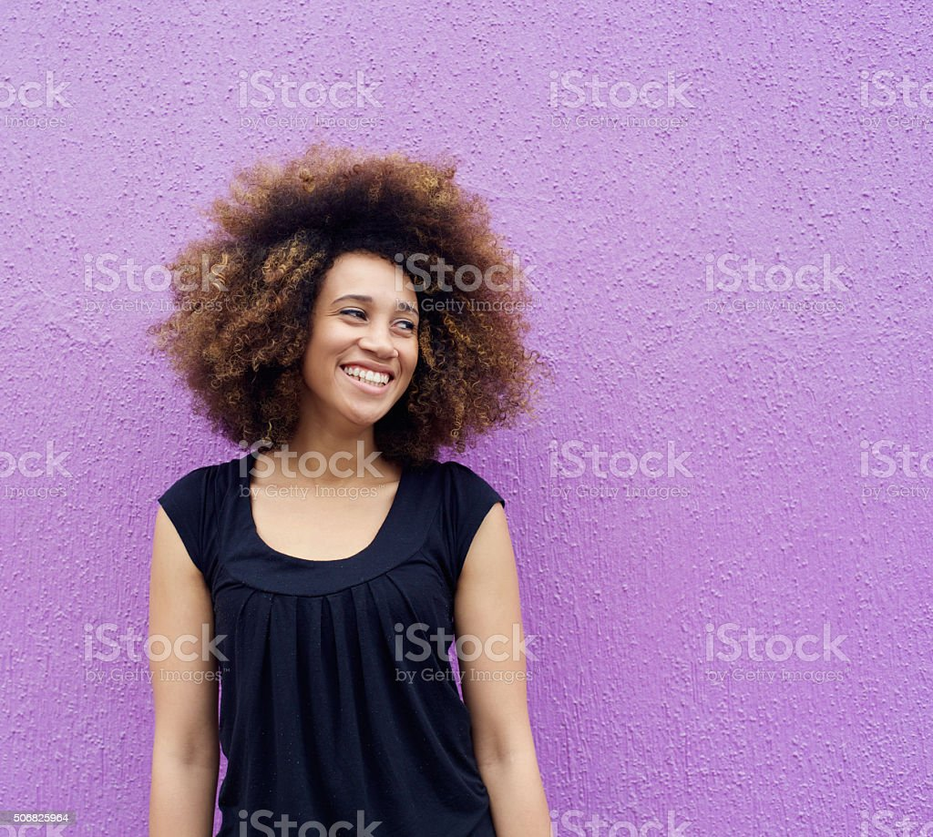 Laughing young woman standing against purple background - Royalty-free 20-29 Years Stock Photo