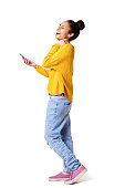 istock Laughing young woman walking with mobile phone 539463432
