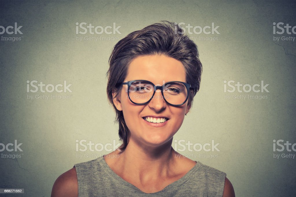 laughing young woman wearing heavy rimmed glasses looking at the camera stock photo